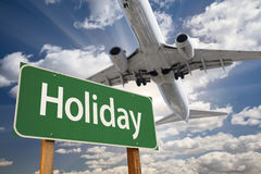Holiday Green Road Sign and Airplane Above Stock Photo