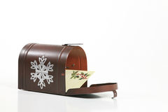 Holiday Greeting. A holiday envelope inside a wintry mailbox isolated against a white background. Space for copy stock photo
