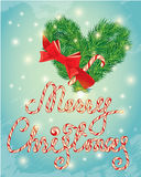 Holiday greeting Card with xmas candy and fir-tree branches. In heart shape. Hand written calligraphic text Merry Christmas on frosen winter background Stock Photo