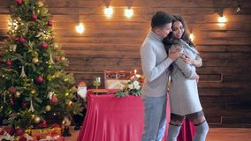 Holiday, guy hugs girl at home on background of illuminated Christmas tree with garlands. Holiday, guy hugs his girl at home on background of illuminated stock footage