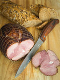 Holiday ham on wooden board, with crunchy cereal bread. Close up stock photo