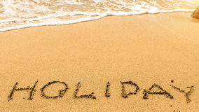 Holiday - hand-written on the sand in line of the sea surf. Abstract. Royalty Free Stock Image