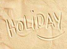 Holiday handwritten in golden beach sand royalty free stock photos