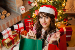 Holiday happy girl after shopping. Christmas holiday happy girl after shopping, in christmas decorated living room ,wear red new year santa hat, over chimney and royalty free stock photo