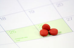 Holiday Headaches. A trio of headache pills sit on a calander on the day after Christmas royalty free stock photos