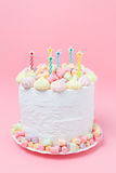 Holiday homemade cake decorated with marshmallow, meringue, candy and candles on a pastel pink background. Birthday cake Stock Photography