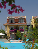 Holiday Hotel Apartments. Holiday apartments of a hotel in Turkey with pool and flowers in the foreground Royalty Free Stock Photos