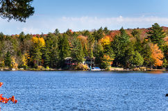 Holiday Houses among Trees on the Shore of a Mountain Lake and Blue Sky Royalty Free Stock Photo