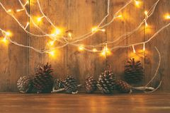 Holiday image with Christmas golden garland lights and pine cones over wooden background.  Royalty Free Stock Images