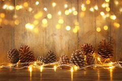 Holiday image with Christmas golden garland lights and pine cones over wooden background.  Stock Photo