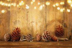 Holiday image with Christmas golden garland lights and pine cones over wooden background stock photos