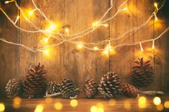 Holiday image with Christmas golden garland lights and pine cones over wooden background.  Stock Photography