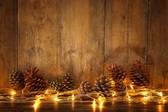 Holiday image with Christmas golden garland lights and pine cones over wooden background stock image