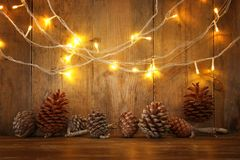 Holiday image with Christmas golden garland lights and pine cones over wooden background.  royalty free stock photography