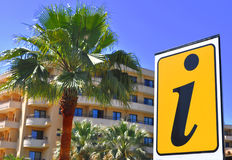 Holiday information. Yellow information sign in front of a palm and holiday apartments Stock Photos