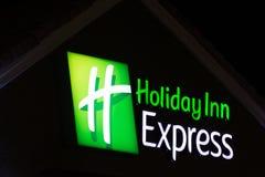Holiday Inn uttryckligt tecken på natten arkivfoton