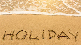Holiday - inscription by hand on yellow beach sand. Happy. Royalty Free Stock Photography
