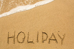 HOLIDAY inscription on the sea beach sand Royalty Free Stock Photo