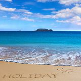HOLIDAY insctiption under the sun drawing on wet beach sand with Stock Images