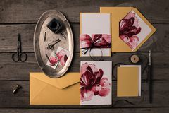 Holiday invitations with floral illustrations. Composition of holiday invitations with floral illustrations and decorative tools on rustic wooden table Stock Images
