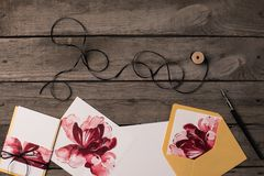 Holiday invitations with floral illustrations. Composition of holiday invitations with floral illustrations and thread on rustic wooden table Stock Photo