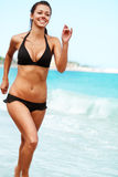 Holiday jogging. Young attractive woman jogging on the beach royalty free stock photos