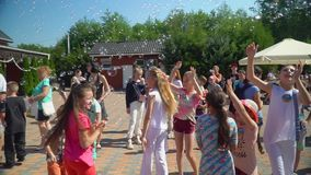 Holiday kids in park, happy children have fun outdoors playing and jumping with soap bubbles while relaxing on summer