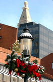 Holiday Lamp Post. A old fashioned lampost is decorated for Christmas with a steeple in the background Royalty Free Stock Photo