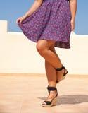 Holiday legs. Tanned female legs in high heels, flared short skirt Stock Image