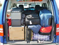 Holiday luggage. Suitcases and bags in the luggage boot of a car Stock Photos