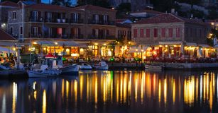 Holiday makers dining in harbor side restaurants Molyvos Greece stock image