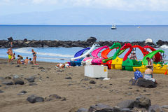Holiday makers enjoy the welcome relief of an overcast sky as the sunbath on the sandy beach at Playa Las Americas in Teneriffe in Royalty Free Stock Images