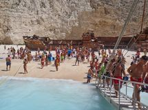 Sandy Navagio Beach, Zakynthos Greek Island, Greece. Holiday makers and graffiti covered rusted shipwreck at Navagio, or Wreck, Beach on Zakynthos, an Ionian stock photography