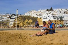 Holiday makers relaxing in the sun on the beach at the Old Townin Albuferia, Portugal royalty free stock photo