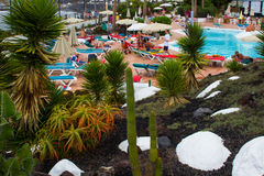 Holiday makers relaxing in the sun at a hotel pool beside a beautiful Cacti and Rock garden. The cacti have been cultivated in a volcanic rock substate that Royalty Free Stock Photography