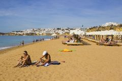 Holiday makers relaxing in the sun on the Praia Azul beach in Albuferia, Portugal. Holiday makers relaxing while enjoying the sun on the Praia Azul beach in Stock Images