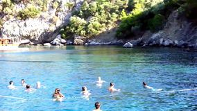 Holiday makers swimming in blue waters. Holiday makers swim in the blue waters of Aegean sea   during the swimming break of a Daily Boat tour which is popular in stock video