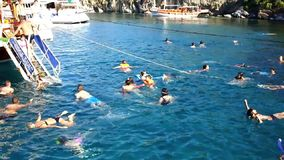 Holiday makers swimming in blue waters. Holiday makers swim in the blue waters of Aegean sea   during the swimming break of a Daily Boat tour which is popular in stock video footage