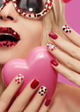 Holiday makeup and manicure with red hearts Royalty Free Stock Image