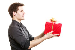 Holiday. Man giving gift box with golden ribbon Royalty Free Stock Photos