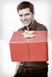 Holiday. Man giving gift box with golden ribbon Royalty Free Stock Image