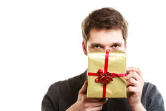 Holiday. Man giving golden gift box with ribbon Stock Photo