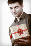 Holiday. Man giving golden gift box with ribbon Royalty Free Stock Image