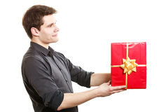 Holiday. Man giving red gift box with golden ribbon Stock Photo