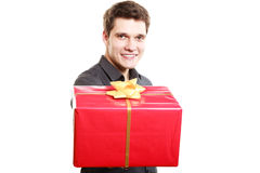 Holiday. Man giving red gift box with golden ribbon Stock Photography