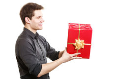 Holiday. Man giving red gift box with golden ribbon Stock Images