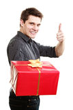 Holiday. Man giving red gift box showing thumb up Stock Photos