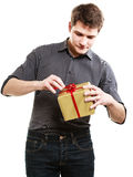 Holiday. Man got golden gift box with red ribbon Stock Photos