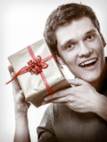 Holiday. Man got golden gift box with red ribbon Royalty Free Stock Photos