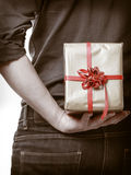 Holiday. Man hiding surprise gift box behind back. Holiday and special occasion. Closeup of male hands. Man giving golden gift box with red ribbon isolated on Stock Photos